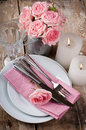 Vintage festive table setting with pink roses candles and cutlery on an old wooden board Stock Photos
