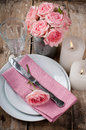 Vintage festive table setting with pink roses candles and cutlery on an old wooden board Stock Image