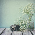 Vintage filtered and toned image of fresh white flowers and old camera over wooden table. Royalty Free Stock Photo