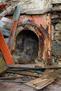 Vintage fireplace surround an ornate metal rusty and painted orange amoungst planks and rubble Stock Photos