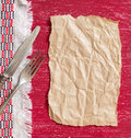 Vintage fork and knife on napkin on red wood and craft paper Royalty Free Stock Photo