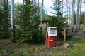 Vintage gas pump red and white setting in evergreen trees Royalty Free Stock Photography