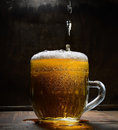 Vintage glass of beer with foam on a wooden board against a dark background Royalty Free Stock Photo