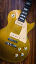 Vintage gold top single cutaway guitar on wood surface Stock Photography