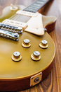 Vintage gold top single cutaway guitar on wood surface Stock Photos