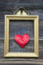Vintage golden picture frame with red heart on wall Royalty Free Stock Photo