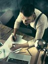 Vintage hipster wooden desktop top view, male hands using a laptop and holding a pencil Royalty Free Stock Photo