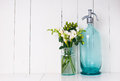 Vintage home decor ancient turquoise siphon freesias bouquet and bottles on a white wooden background Stock Images