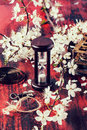 Vintage hourglass with blossom branch and key of cherry tree on black and red wooden table in retro filter effect see series Stock Photography