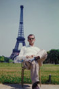 Vintage image of a tourist sitting in front of the eiffel tower paris france s man taken from color slide Royalty Free Stock Photography