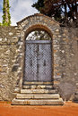 Vintage iron door encased in a stone portal rusty between walls surmounted by arch Stock Photo