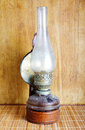 Vintage kerosene lamp on table over wooden background Royalty Free Stock Photos
