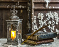 Vintage lamp for the candle and old books on wooden table Stock Photos