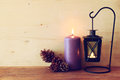 Vintage Lantern with burning Candle and pine cones on wooden table. filtered image Royalty Free Stock Photo
