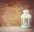 Vintage Lantern with burning candle on wooden table and glitter lights background. filtered image. Royalty Free Stock Photo