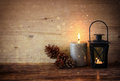 Vintage Lantern with burning candles, pine cones on wooden table and glitter lights background. filtered image Royalty Free Stock Photo