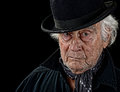 Vintage looking old man with a black coat gray scarf and black bowler hat staring straight at the camera isolated on black Stock Photo