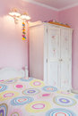 Vintage mansion girly bedroom a with a colorful bed and a white wardrobe Stock Images