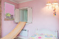 Vintage mansion pink wall apink of a girl s bedroom with a slide a lamp and a painting Stock Photo