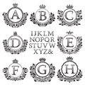 Vintage monogram kit. Black patterned letters and floral coat of arms frames for creating initial logo in antique style Royalty Free Stock Photo