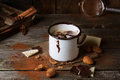 Vintage mug with hot chocolate served chunks of white and dark and almonds on old wooden table Royalty Free Stock Image