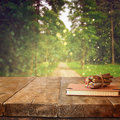 Vintage notebook and stack of wooden colorful pencils on wooden texture table in front of countryside forest view Royalty Free Stock Photo
