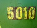 Vintage numbers stenciled on a green rusting and peeling metal steel sheet useful to incorporate into new collage or design led Royalty Free Stock Photo