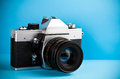 Vintage old film photo camera on blue Stock Photos