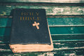 Vintage old holy bible book, grunge textured cover with wooden christian cross. Retro styled image on wood background. Royalty Free Stock Photo