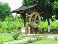 Vintage old wooden water well with huge wheel Royalty Free Stock Photo