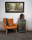 Vintage orange armchair, colorful cupboard, old radio and hanged painting Royalty Free Stock Photo