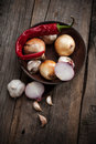 Vintage pepper still life with onion and garlic over grunge wooden background Royalty Free Stock Photo