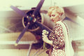 Vintage photo of beautiful girl and plane stylized with a bouquet daisies on background Stock Images