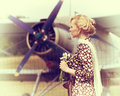 Vintage photo of beautiful girl and plane stylized with a bouquet daisies on background Royalty Free Stock Images