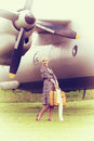 Vintage photo of beautiful girl and plane stylized with yellow suitcase on background Stock Photo