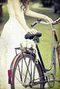 Vintage photo of bride and wedding bouquet on a bicycle