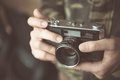 Vintage photo camera in the hands of man, soft focus. Royalty Free Stock Photo