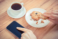 Vintage photo, Hand of woman using mobile phone, oatmeal cookies and cup of coffee Royalty Free Stock Photo
