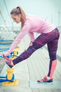 Vintage photo, Slim girl in sports wear exercising in seaport, healthy active lifestyle Royalty Free Stock Photo