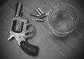 Vintage pistol or gun with booze and bullets whiskey in black white Royalty Free Stock Photography