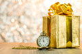 Vintage pocket watch with gold christmas gift box, ribbon and bo Royalty Free Stock Photo