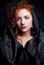 Vintage portrait of glamourous red haired queen like girl a over wrinkled black paper background retro style close up studio shot Royalty Free Stock Images