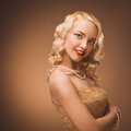 Vintage portrait. Young lady with a gold dress. Pearl beads. Royalty Free Stock Photo