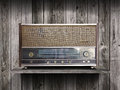 Vintage radio receiver device on old wooden shelf Stock Image