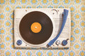 Vintage record player on top of flower wallpaper Royalty Free Stock Photo