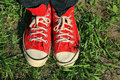 Vintage red sneakers feet in in green grass Stock Photos