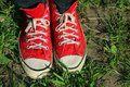 Vintage red sneakers feet in in green grass Stock Photo