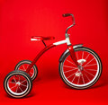 Vintage red tricycle on a bright red background Stock Photography