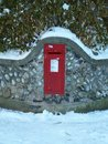 Vintage red UK post box set in stone wall in the snow Royalty Free Stock Photo