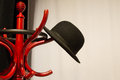 Vintage red wooden coat rack one black hat hang on Stock Photo